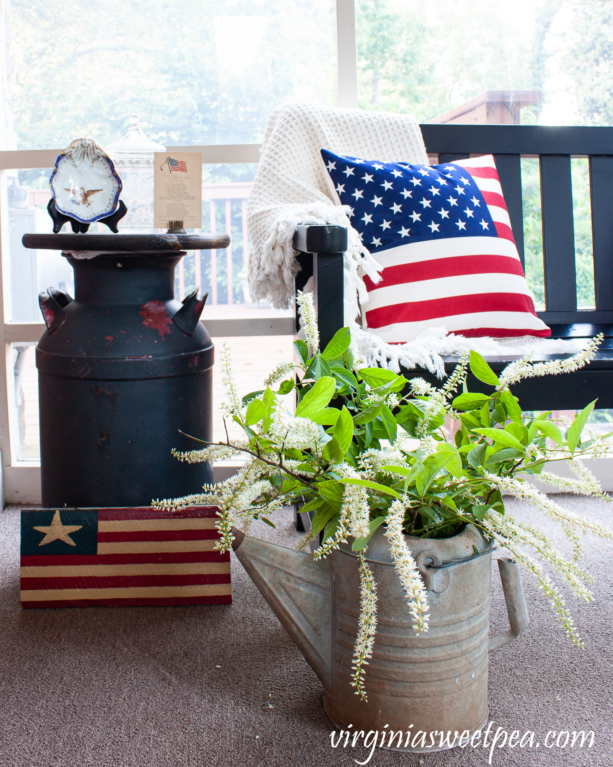 Patriotic porch decor including American flag pillows, a flag sign, a vintage milk can made into a table, and a vintage watering can.
