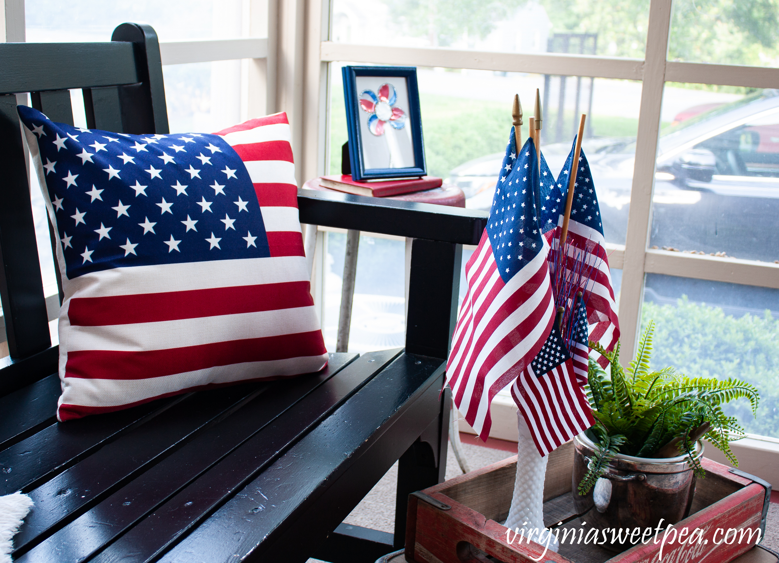 American flag pillow, American flags displayed in a milk glass, vase, adn a Coke crate