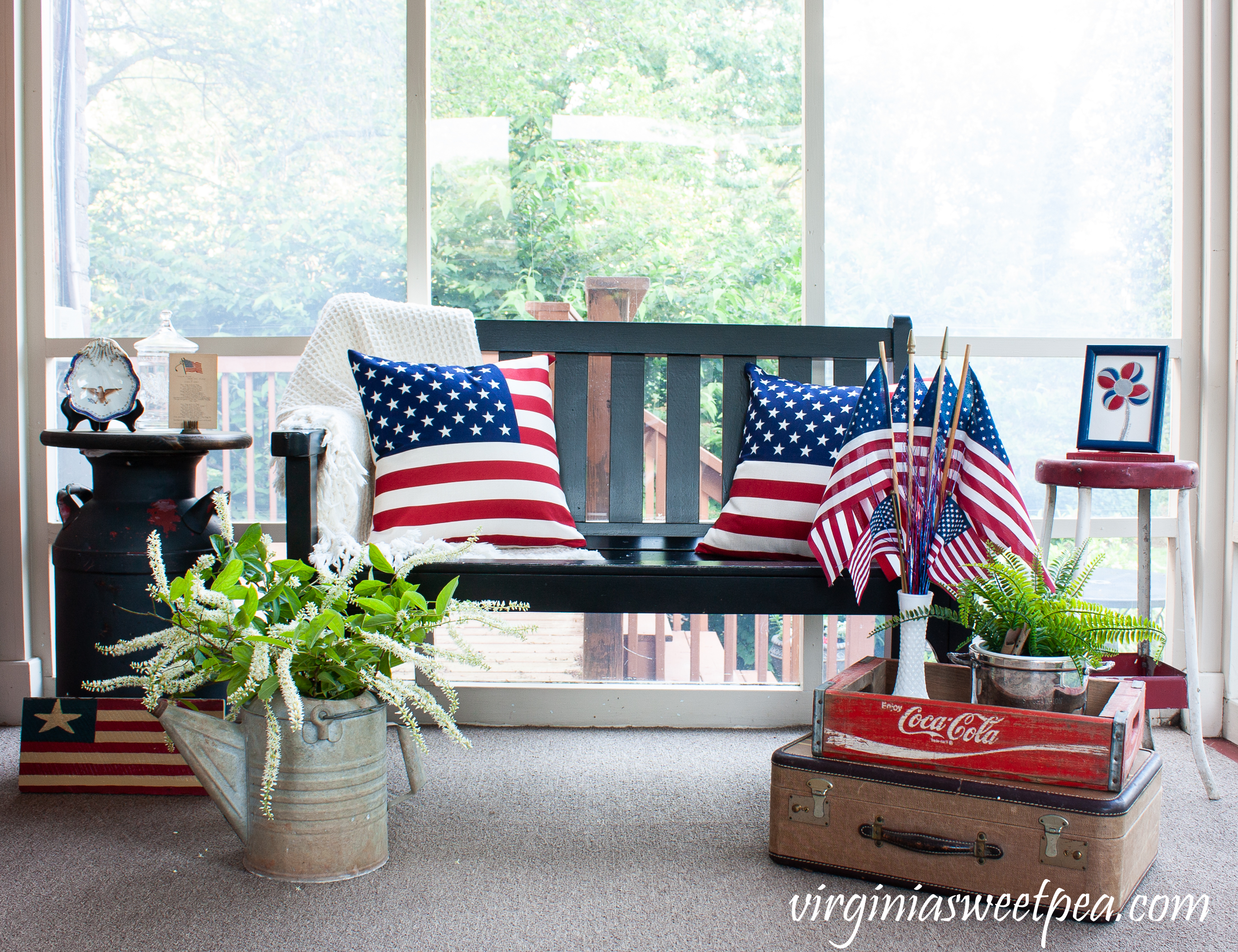 A porch is decorated patriotically with red, white, and blue and with vintage for July 4 and Memorial Day.