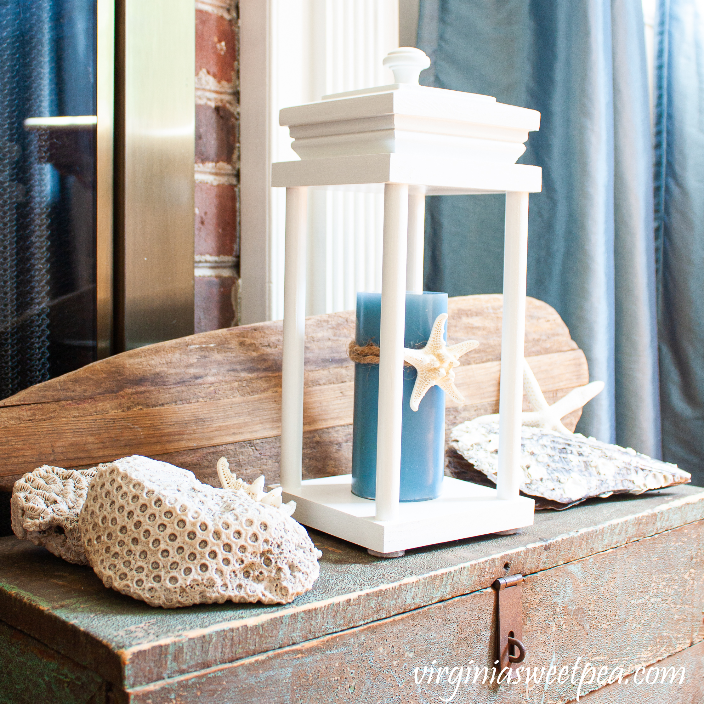 Coastal themed summer vignette with a lantern, shells, coral, and an old wooden oar.