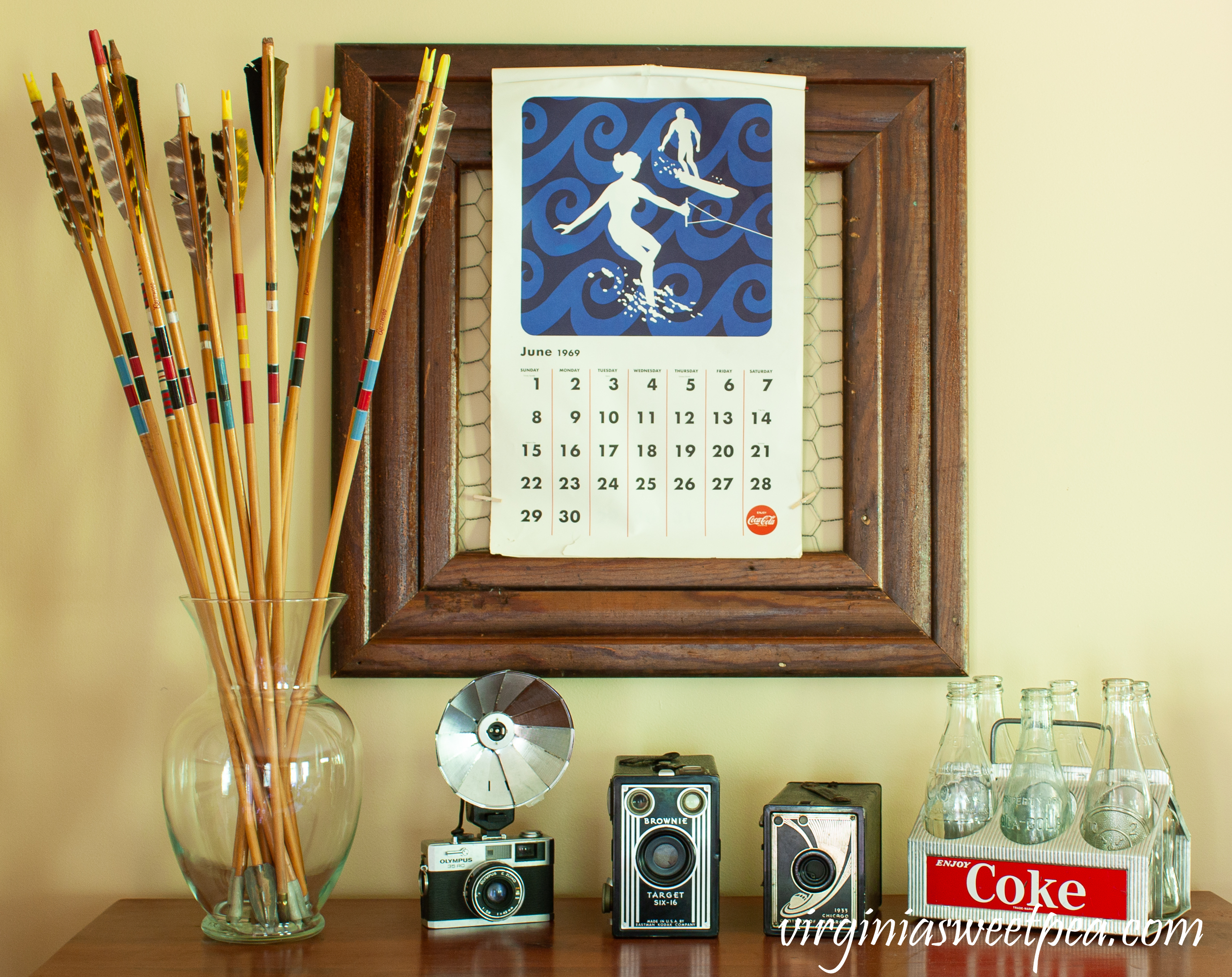 Summer Decorating with Vintage - Summer decor including vintage arrows, vintage cameras, a vintage Coke caddy, and a June Coca-Cola 1969 calendar page.