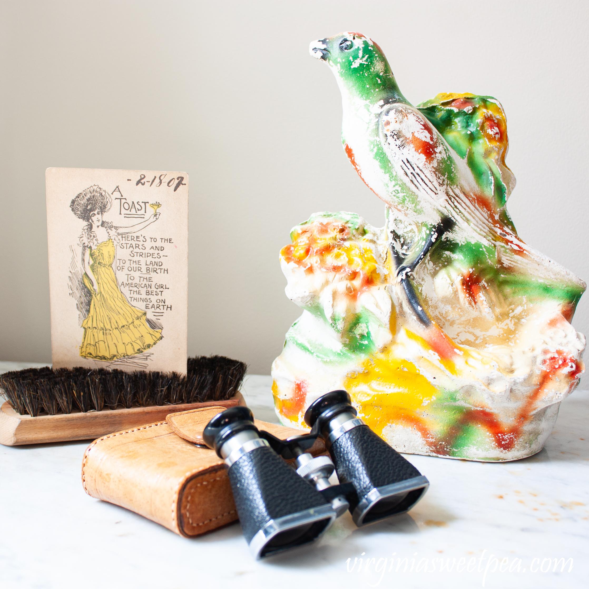 Chalkware bird, vintage binoculars, and a 1907 postcard