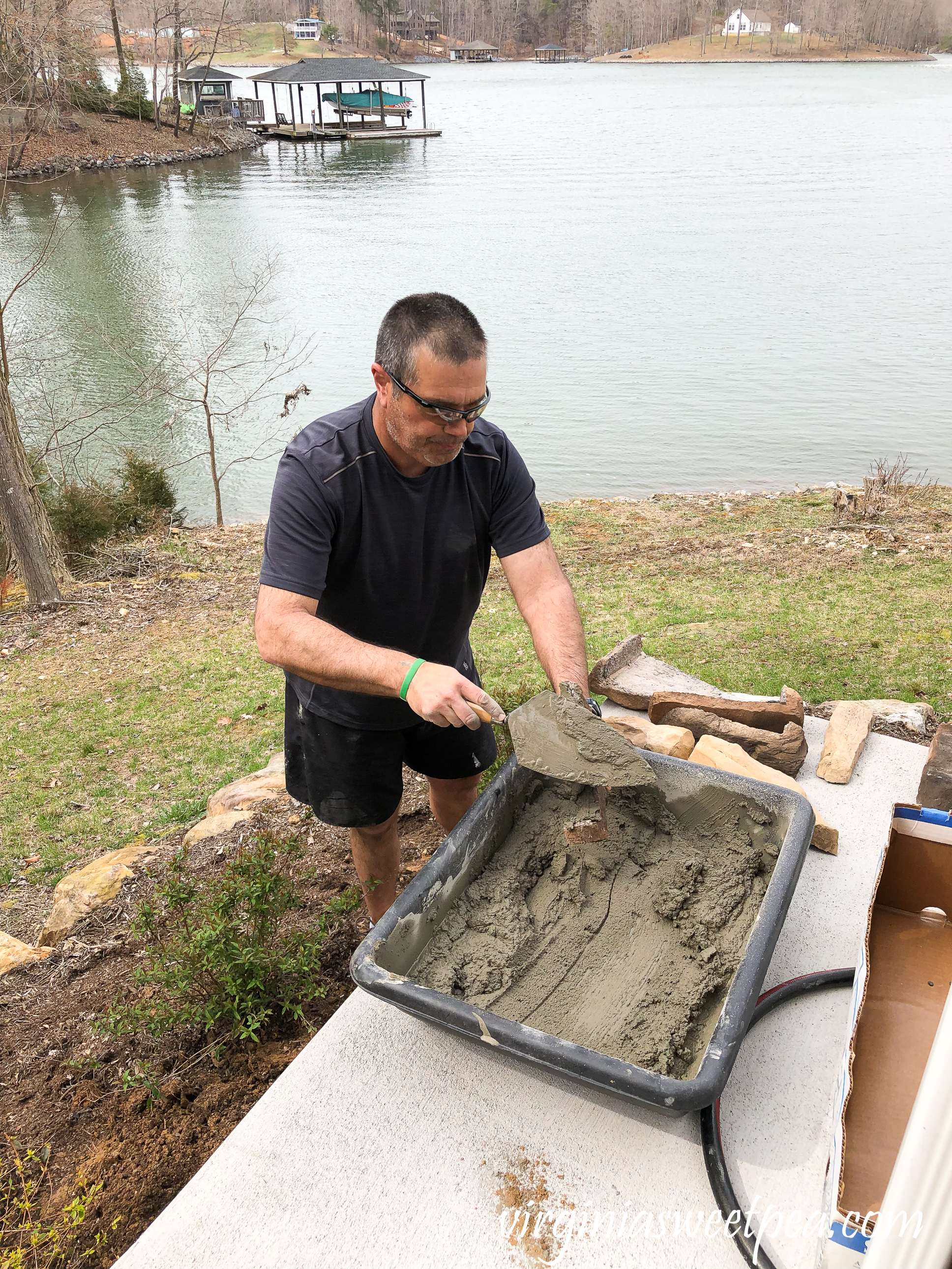 Mixing concrete to use to add stone veneer added to a patio wall