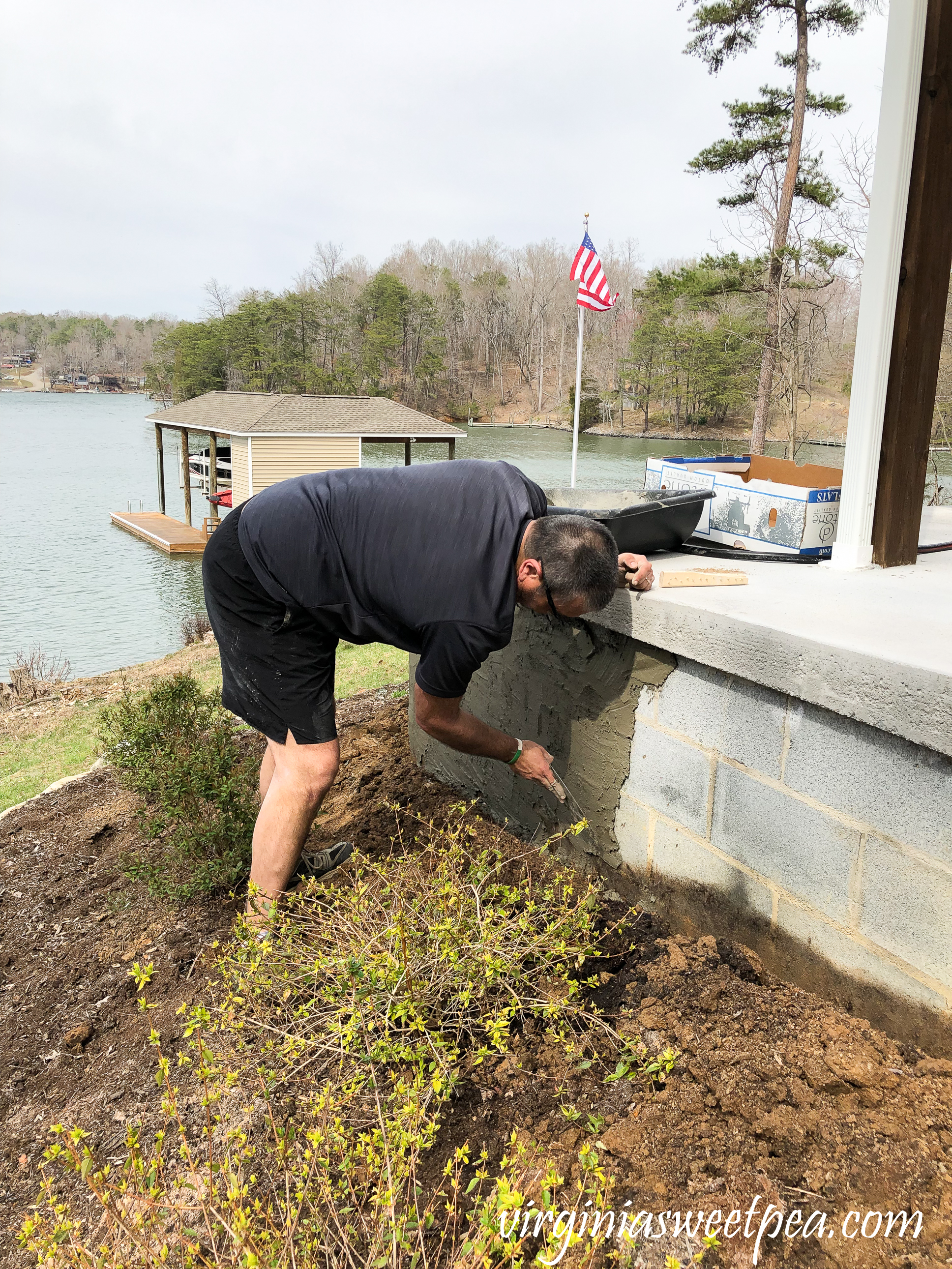Adding a skim coat of concrete to a patio wall.