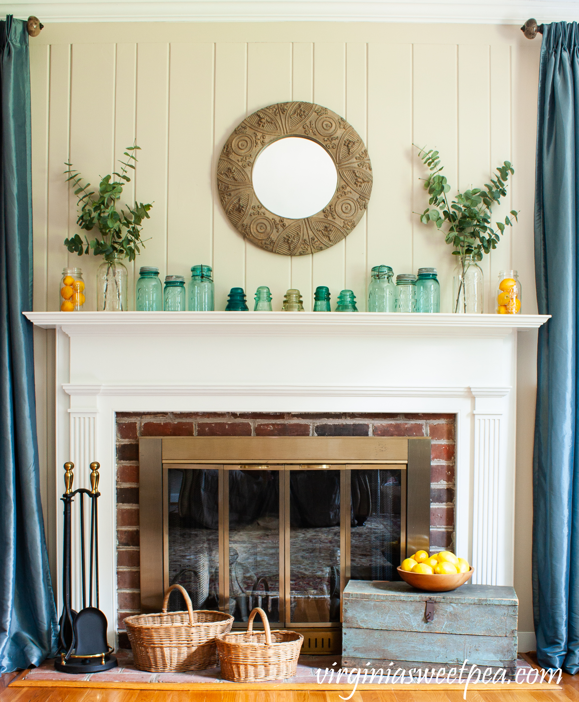 Summer mantel with vintage canning jars, baskets, lemons, eucalyptus, and a vintage tool box.