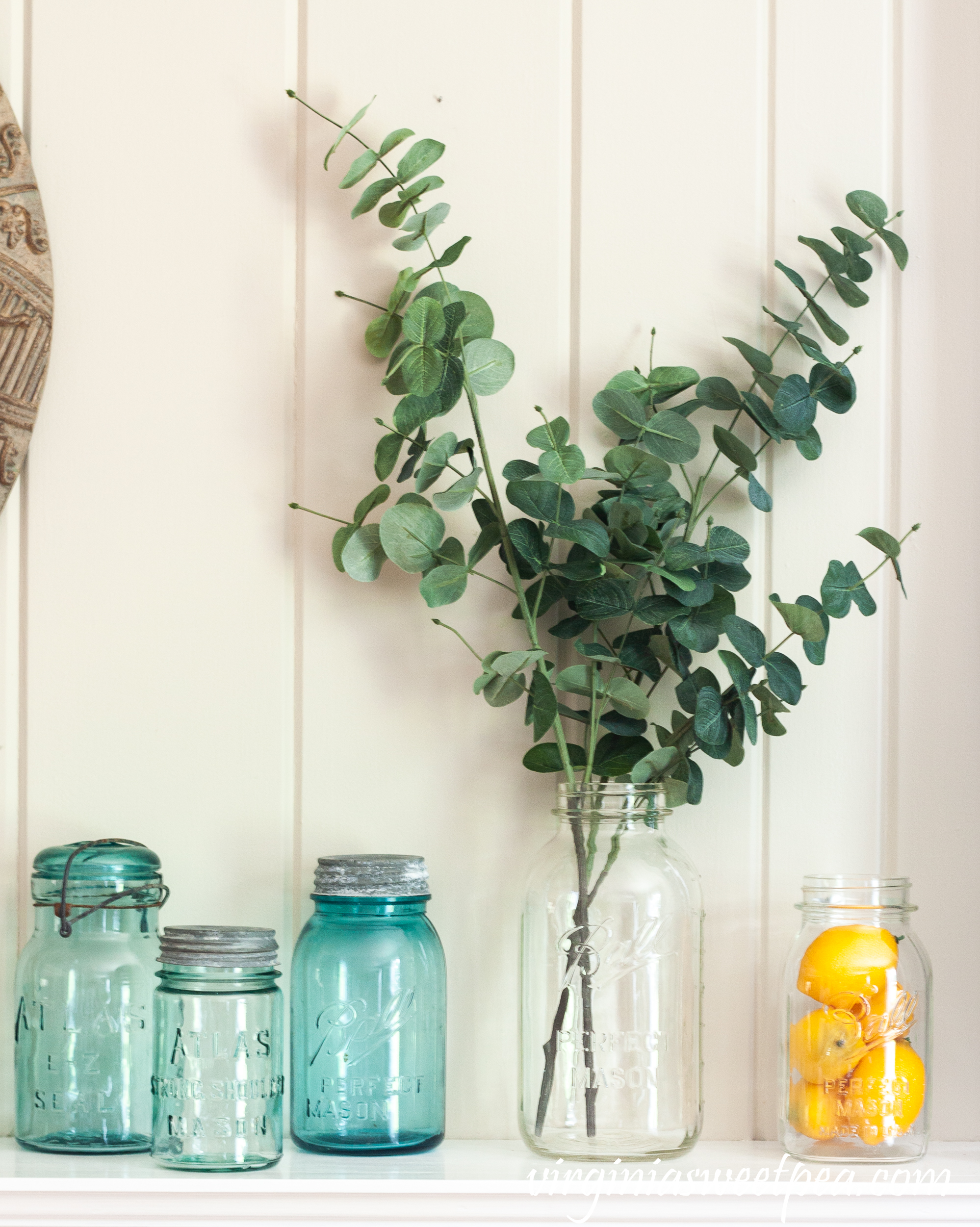 Summer Mantel Decorated with Blue and clear glass Ball Jars, insulators, and lemons.