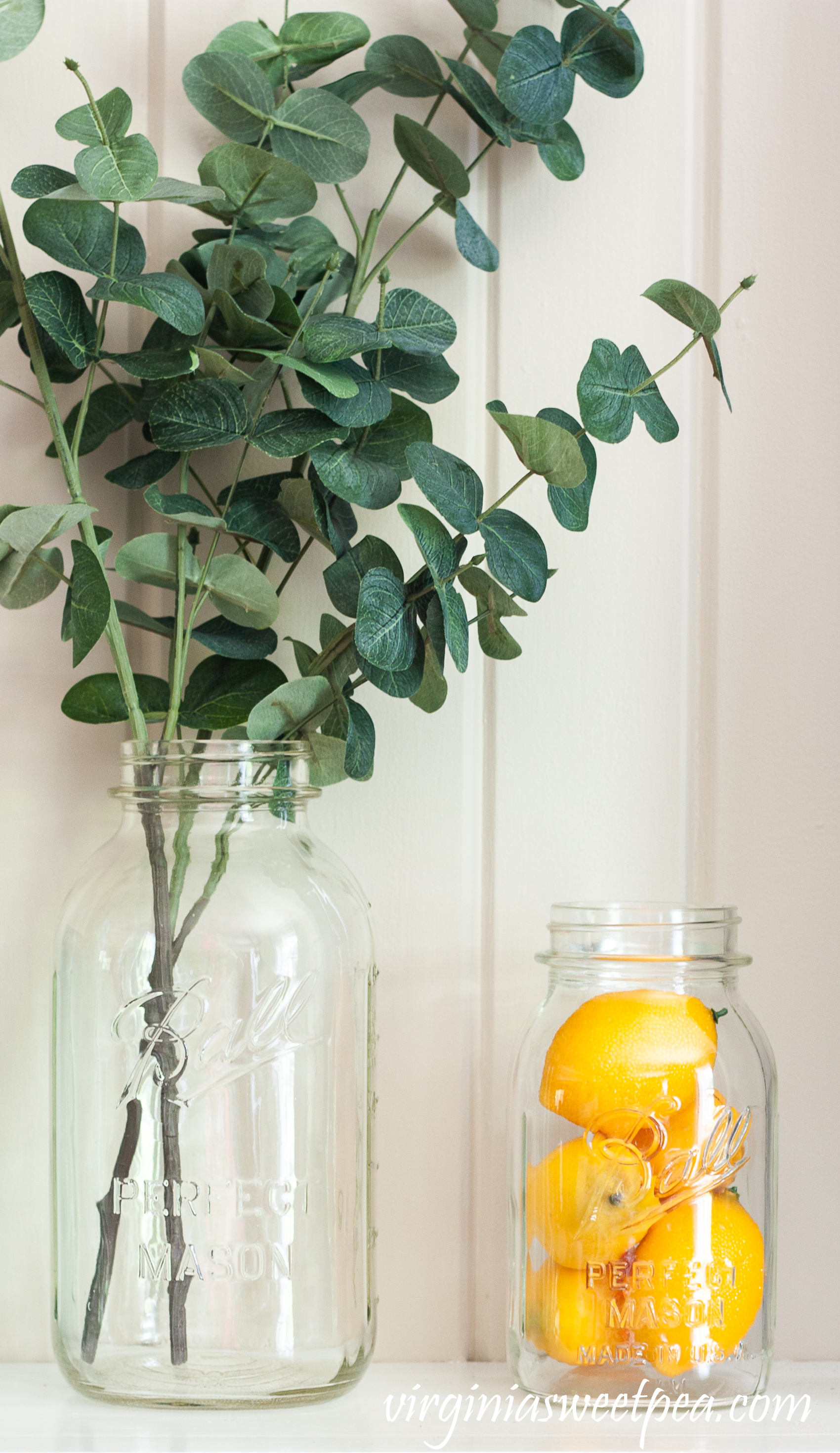 Summer mantel with Ball jars, lemons, and eucalyptus.