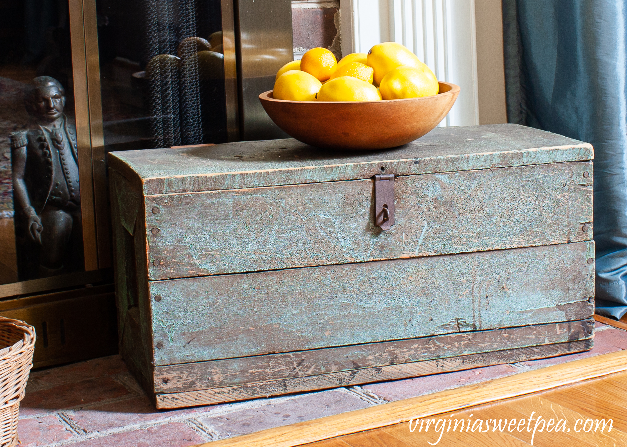 Antique tool box on a fireplace hearth with a wooden bowl filled with lemons.