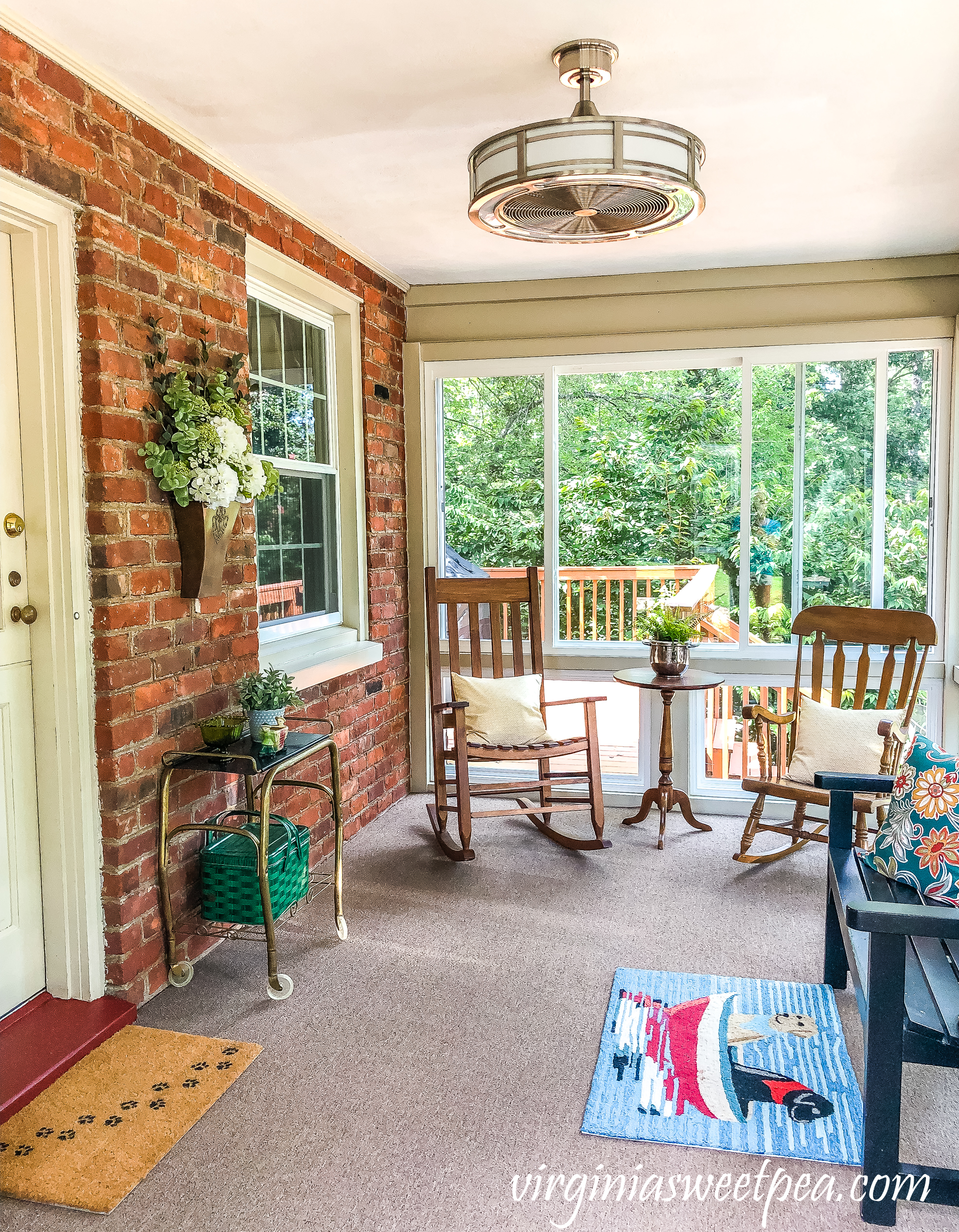 "Home Decorators Collection Brette 23"" Indoor/Outdoor Brushed Nickel fan from Home Depot installed in a sunporch."