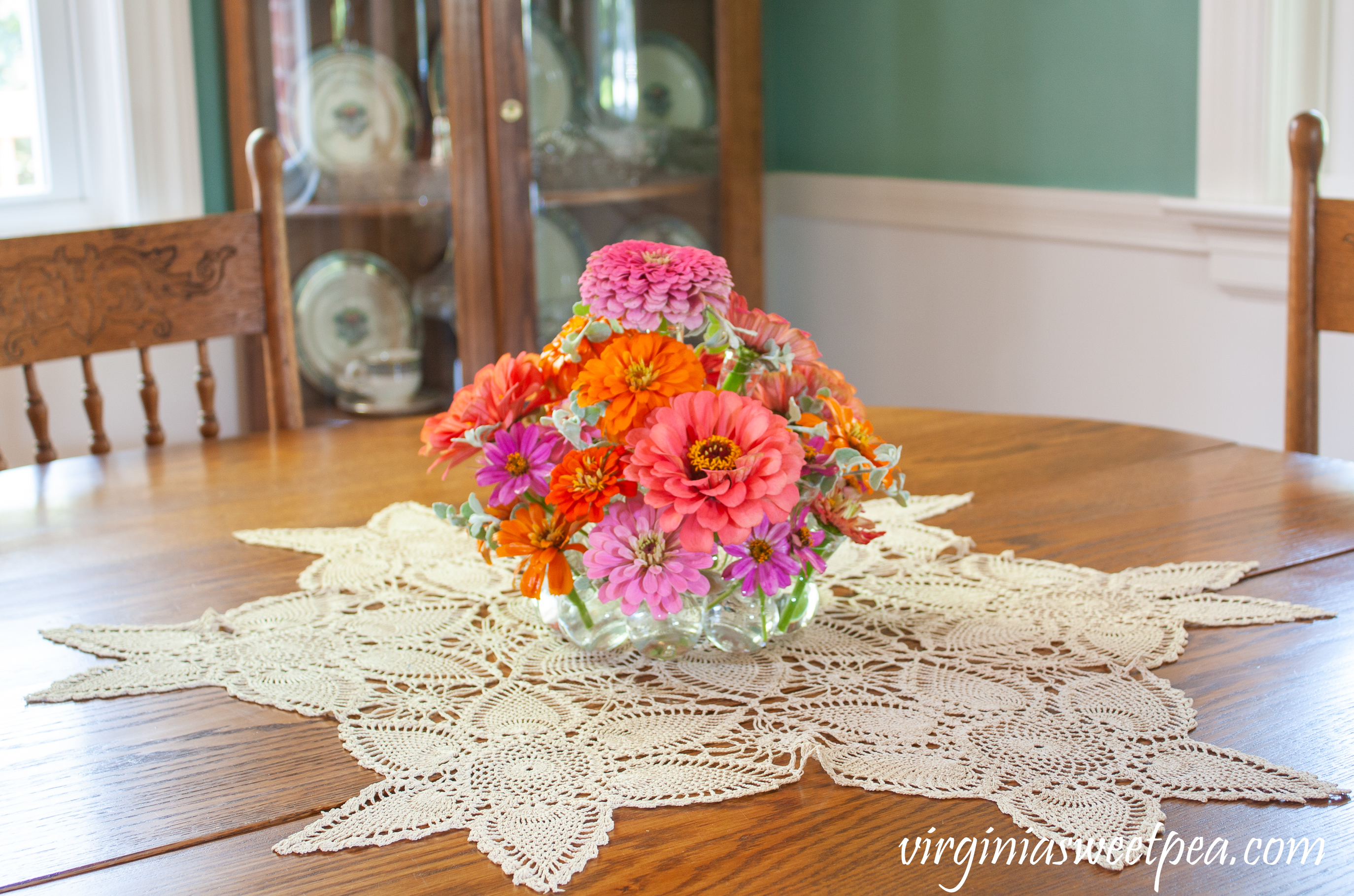 Summer flower arrangement with Zinnias on a dining room table.
