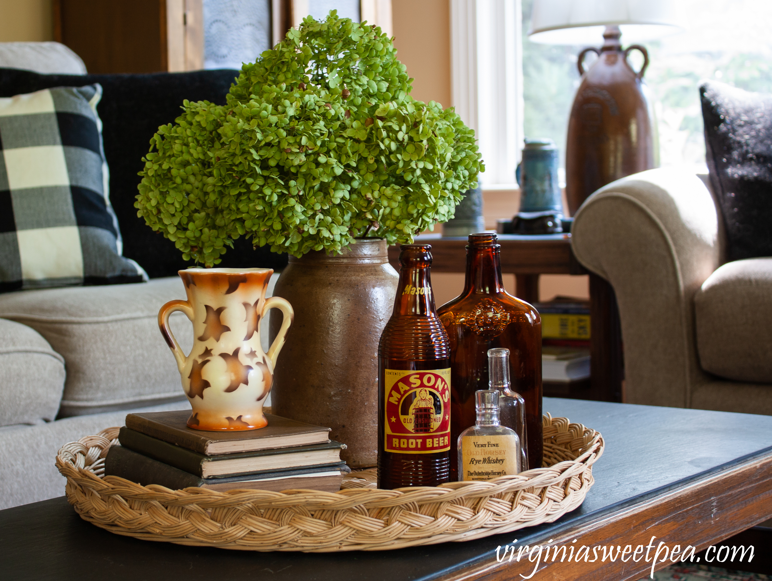 Fall coffee table decor with Hydrangea in a vintage crock, a stack of books with a vintage vase, and three vintage bottles