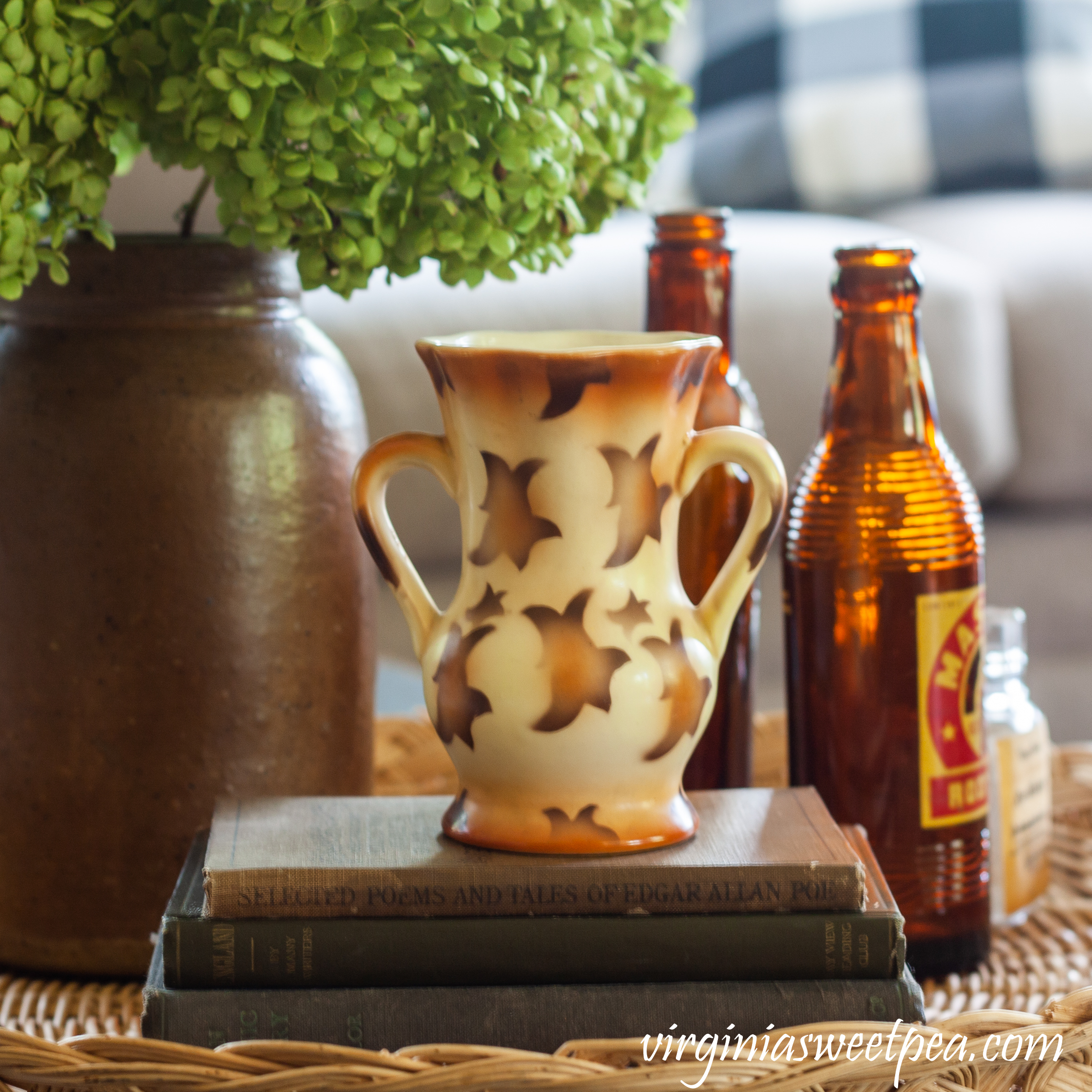 Fall vignette with vintage books and bottles, a Czechoslovakian vase, and a crock filled with Hydrangea.