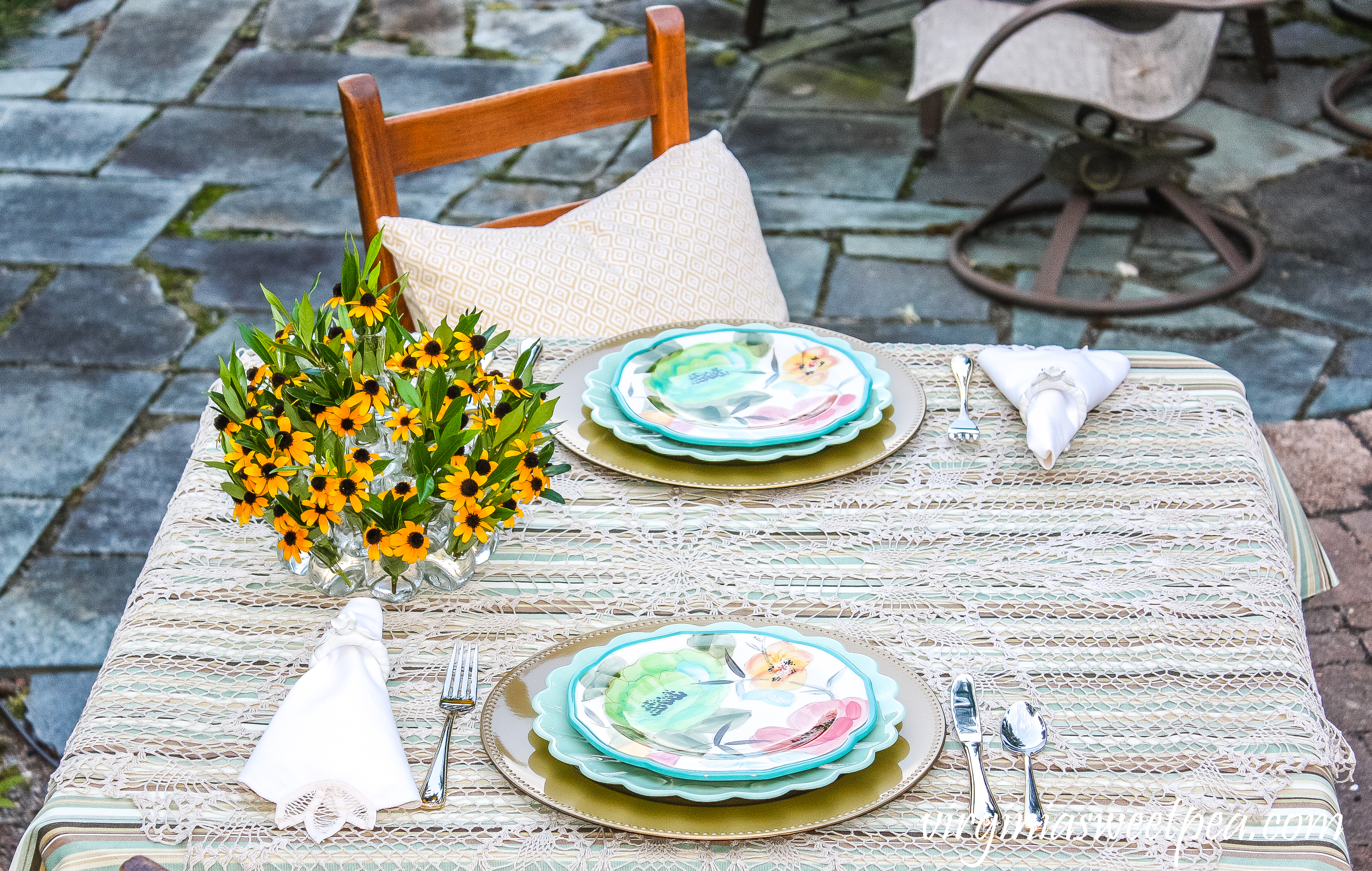 Summer tablescape set in a yard with Pioneer Woman dishes and a floral centerpiece.