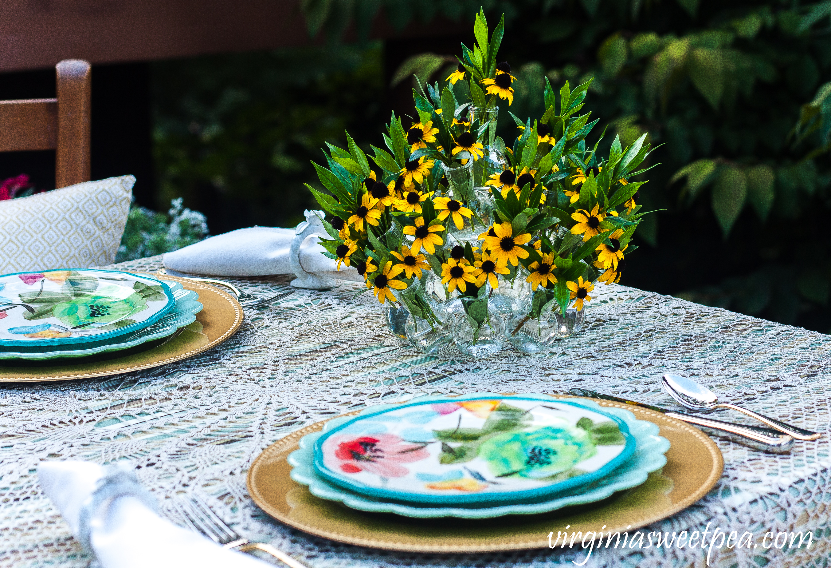 End of summer tablescape set outdoors with Pioneer Woman dishes and a Rudbeckia and Gardenia foliage centerpiece