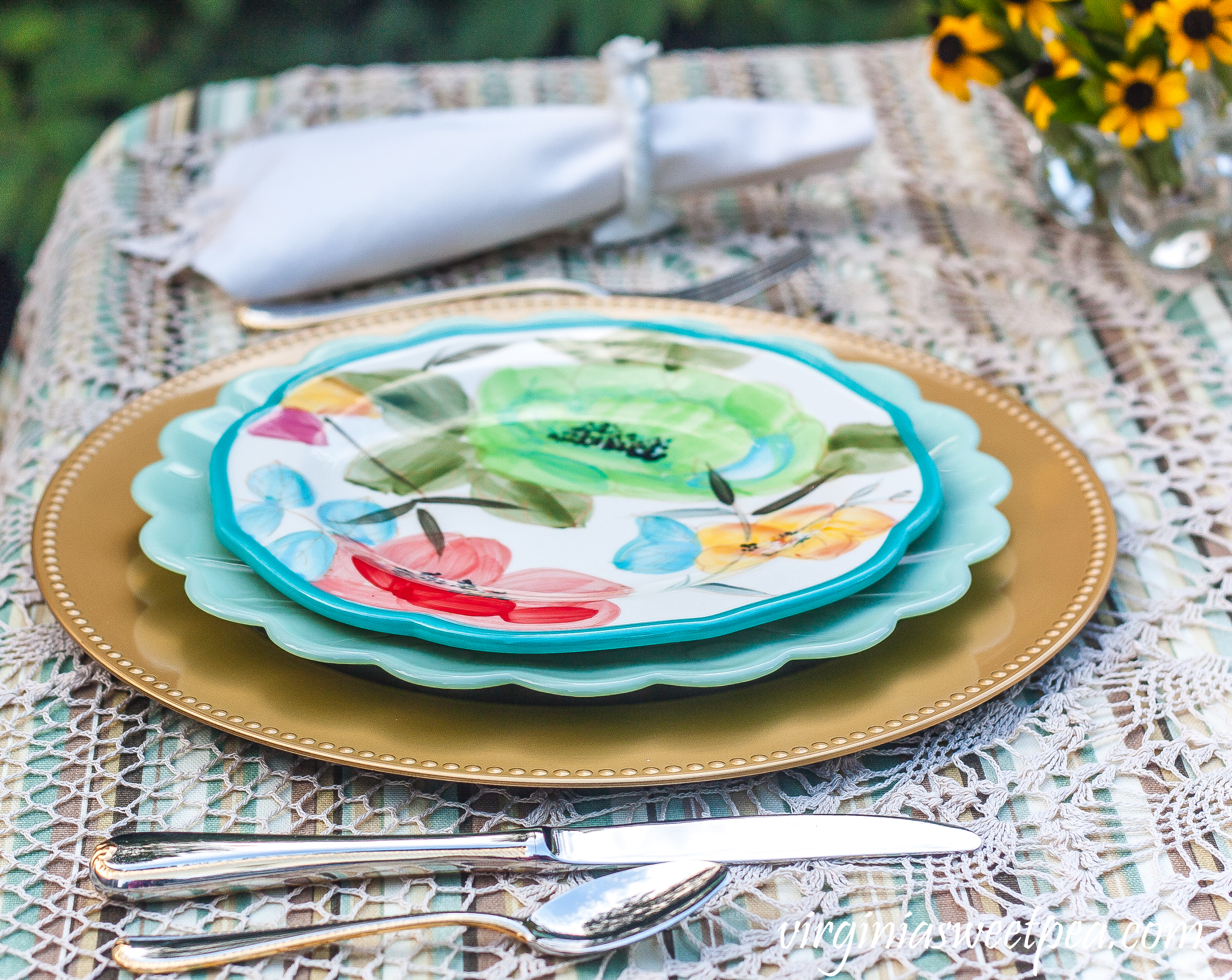 Table setting with Pioneer Woman dishes and Gorham Golden Ribbon Edge flatware.