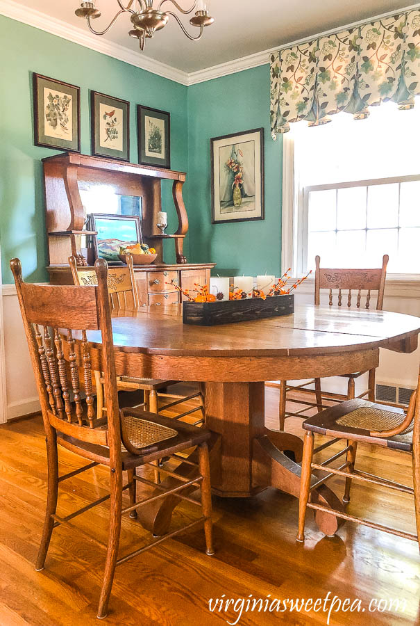 A dining room with antique oak furniture decorated for fall
