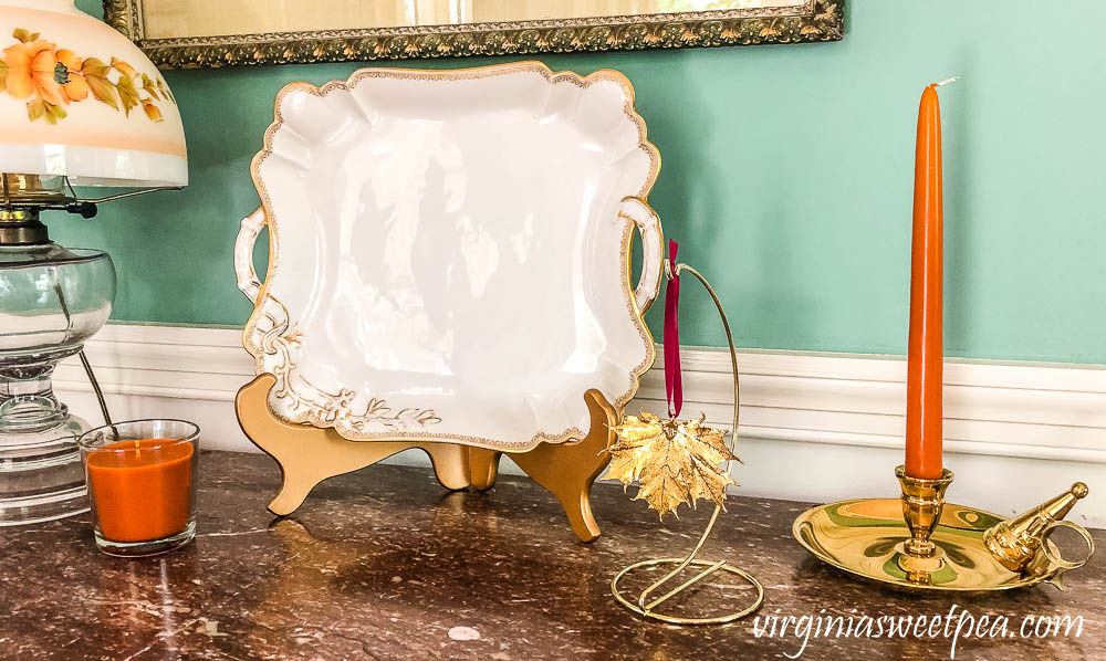 Fall vignette with a Haviland platter, gold preserved Vermont maple leaf ornament, brass candle holder, and an IKEA candle