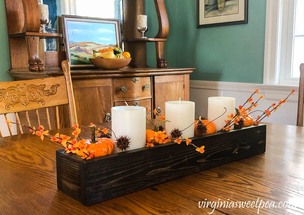 A DIY wood box filled with candles, pumpkins, bittersweet, and sweet gum balls is used as a table centerpiece.