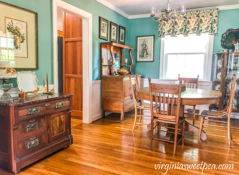 A dining room with antique furniture decorated for fall