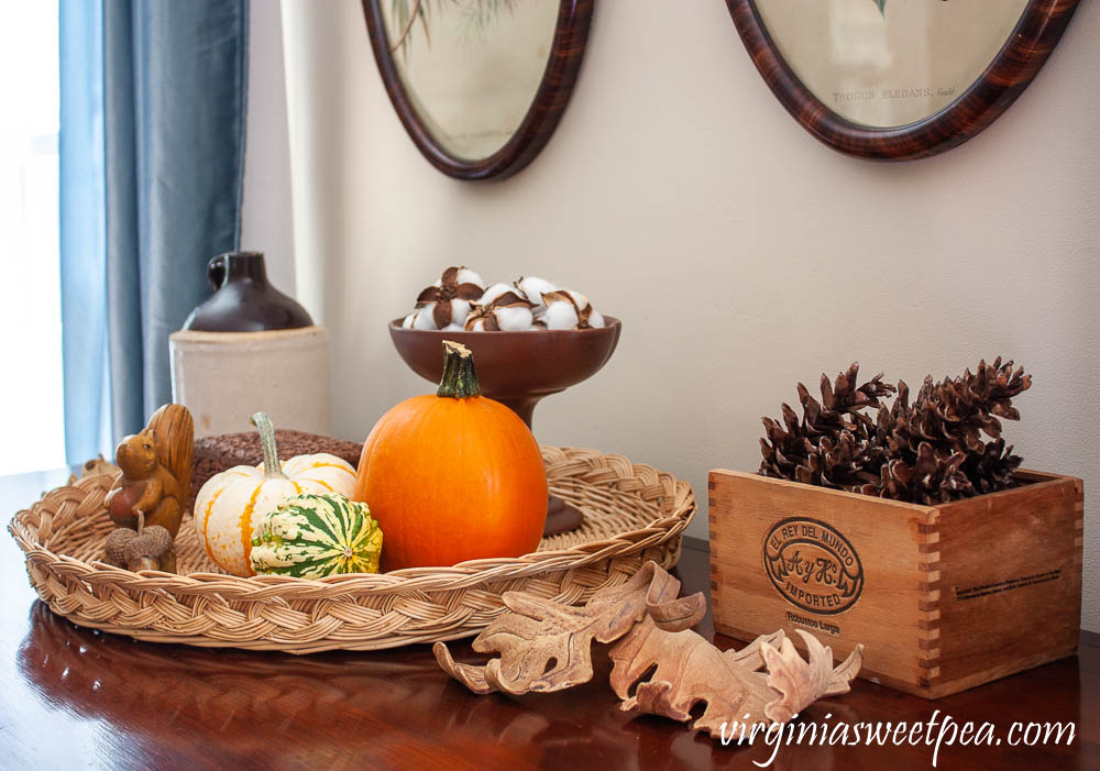 Fall Vignette with an antique jug, handcrafted clay leaves, pumpkins and gourds, a wooden squirrel, wood box from India, a Hagar compote with cotton bolls and a cigar box filled with pinecones