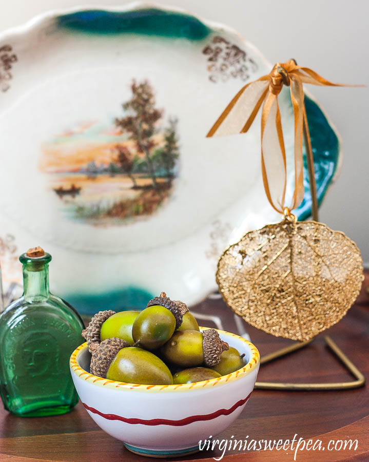 Fall vignette with a small fall plate, vintage bottles, a leaf leaf ornament from Vermont, and a bowl filled with faux acorns
