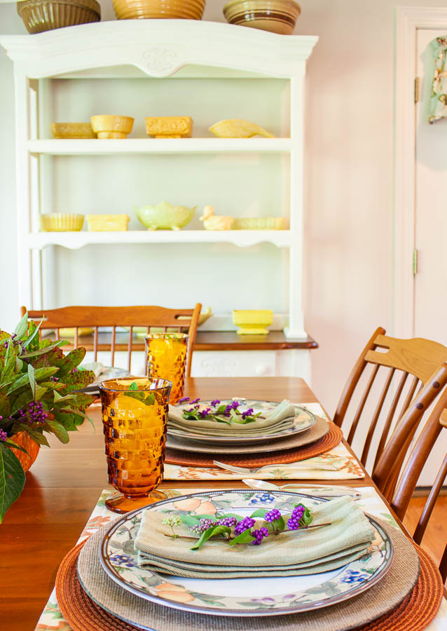 A table set for fall with a painted hutch filled with antique mixing bowls and a collection of yellow vintage flower pots