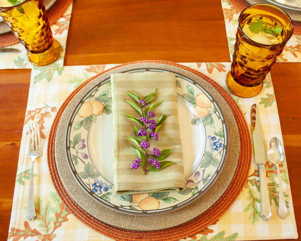 Table setting for fall with placemats printed with leaves, a round orange placemat, burlap charger, Mikasa Garden Harvest dishes, vintage silver, amber Anchor Hocking vintage glasses, and a napkin with a sprig of Beautyberry on top.