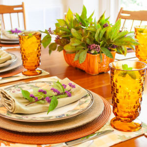 Table set for fall with Mikasa Garden Harvest dishes, vintage amber Anchor Hocking glasses, a centerpiece with Beautyberry and Virginia Sweetspire and layered fall colored placemats and chargers.