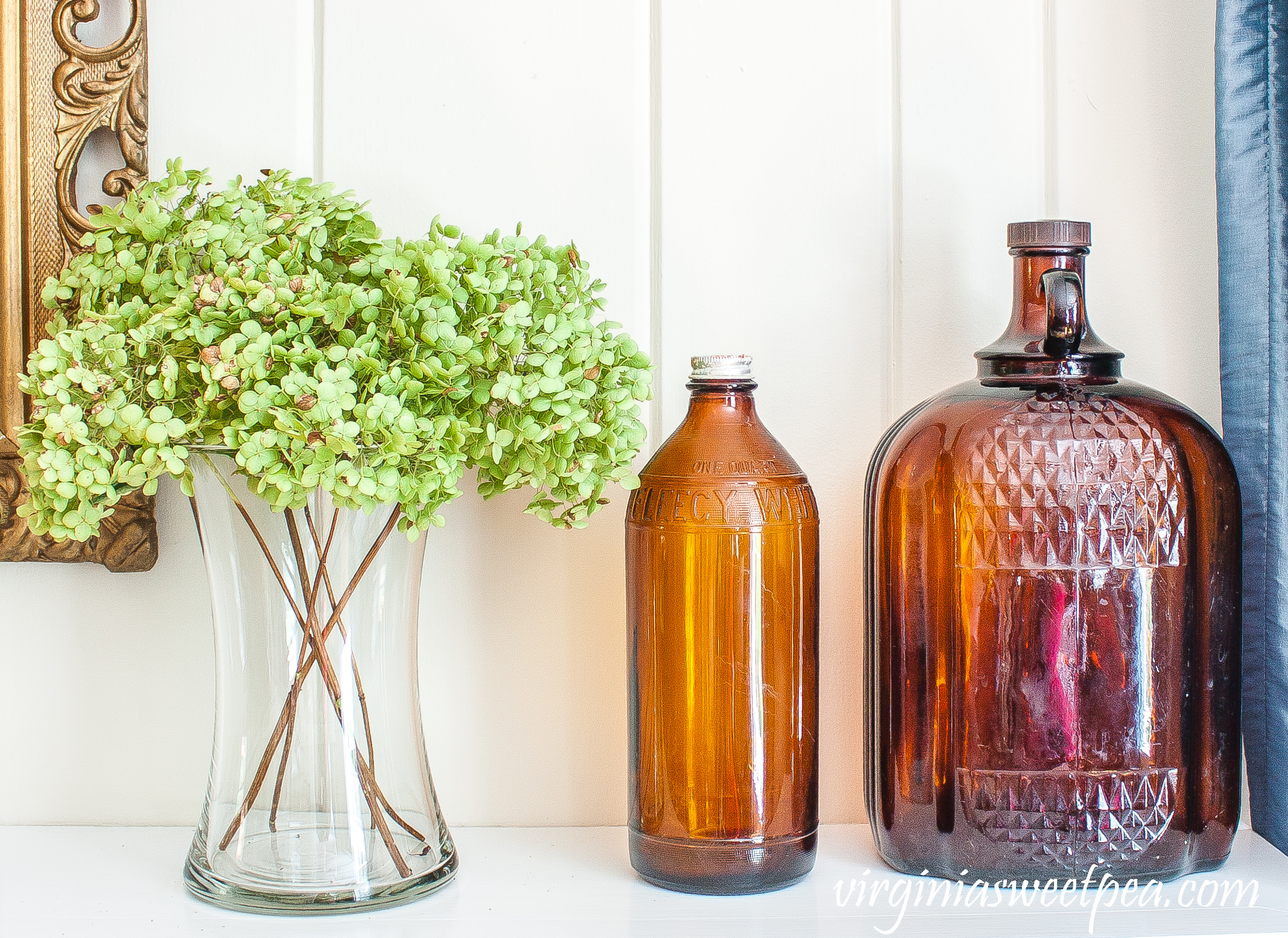Mantel decorated with Hydrangea in a vase and two vintage brown bottles.