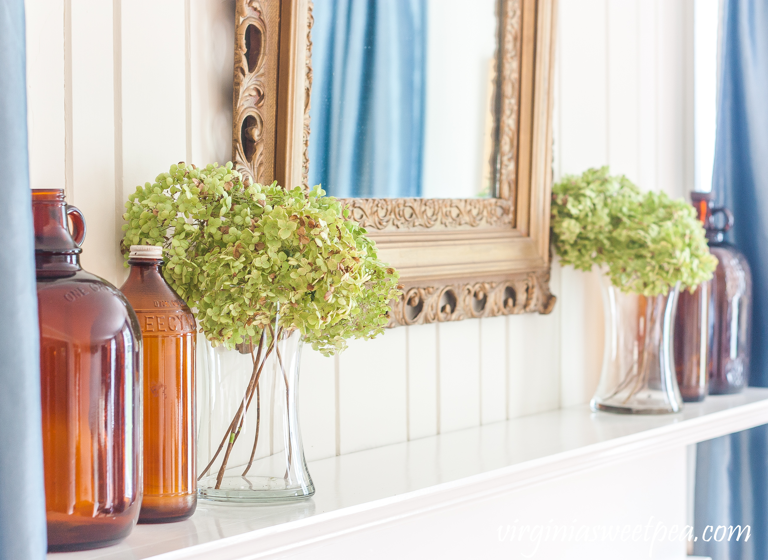 Mantel decorated for early fall with Hydrangea and brown glass bottles.