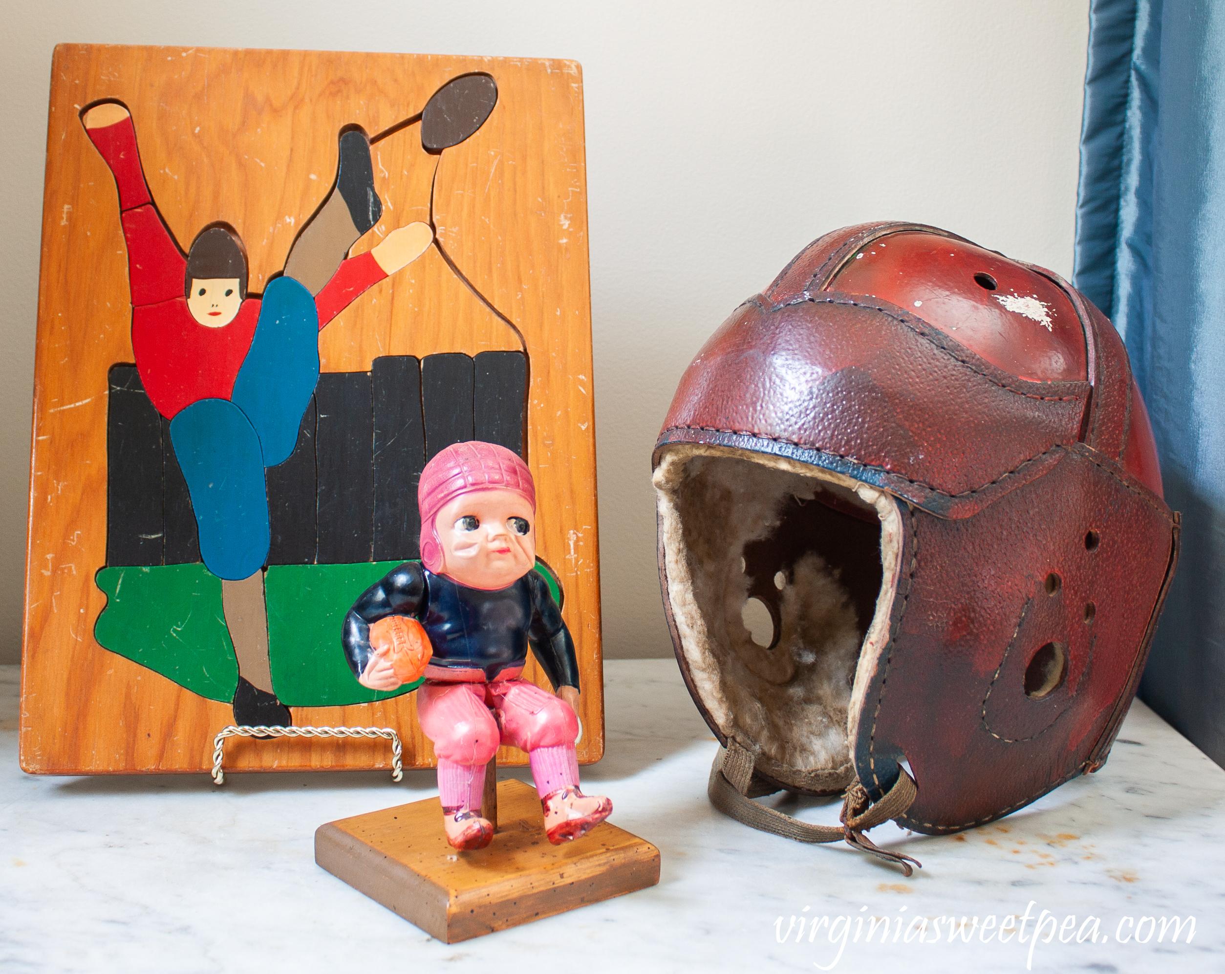 Vintage football vignette with a 1940's football puzzle, 100 year old football toy, and a vintage football helmet