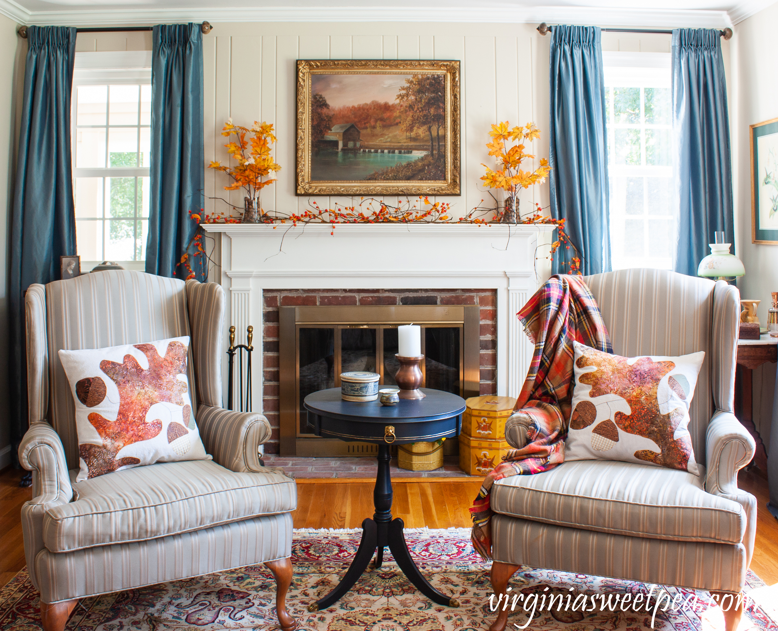 Traditional Fall Mantel - A mantel is decorated for fall with fall foliage anchored in glass vases filled with acorns along with bittersweet, mums, vintage hat boxes, and a vintage painting of a mill in Sussex County, NJ.