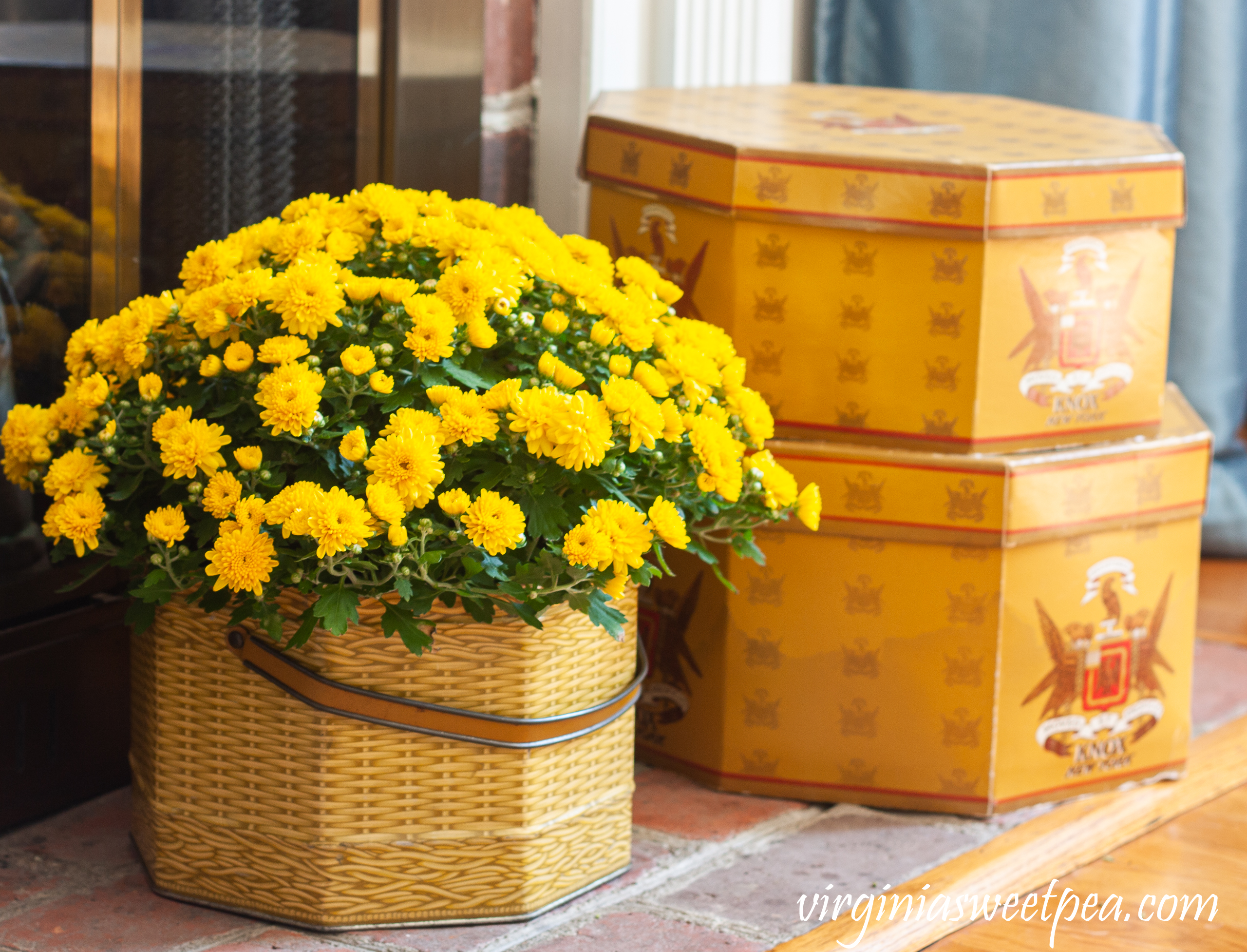 Knox New York hat boxes along with a mum in a vintage basket tin decorate a fireplace hearth for fall.