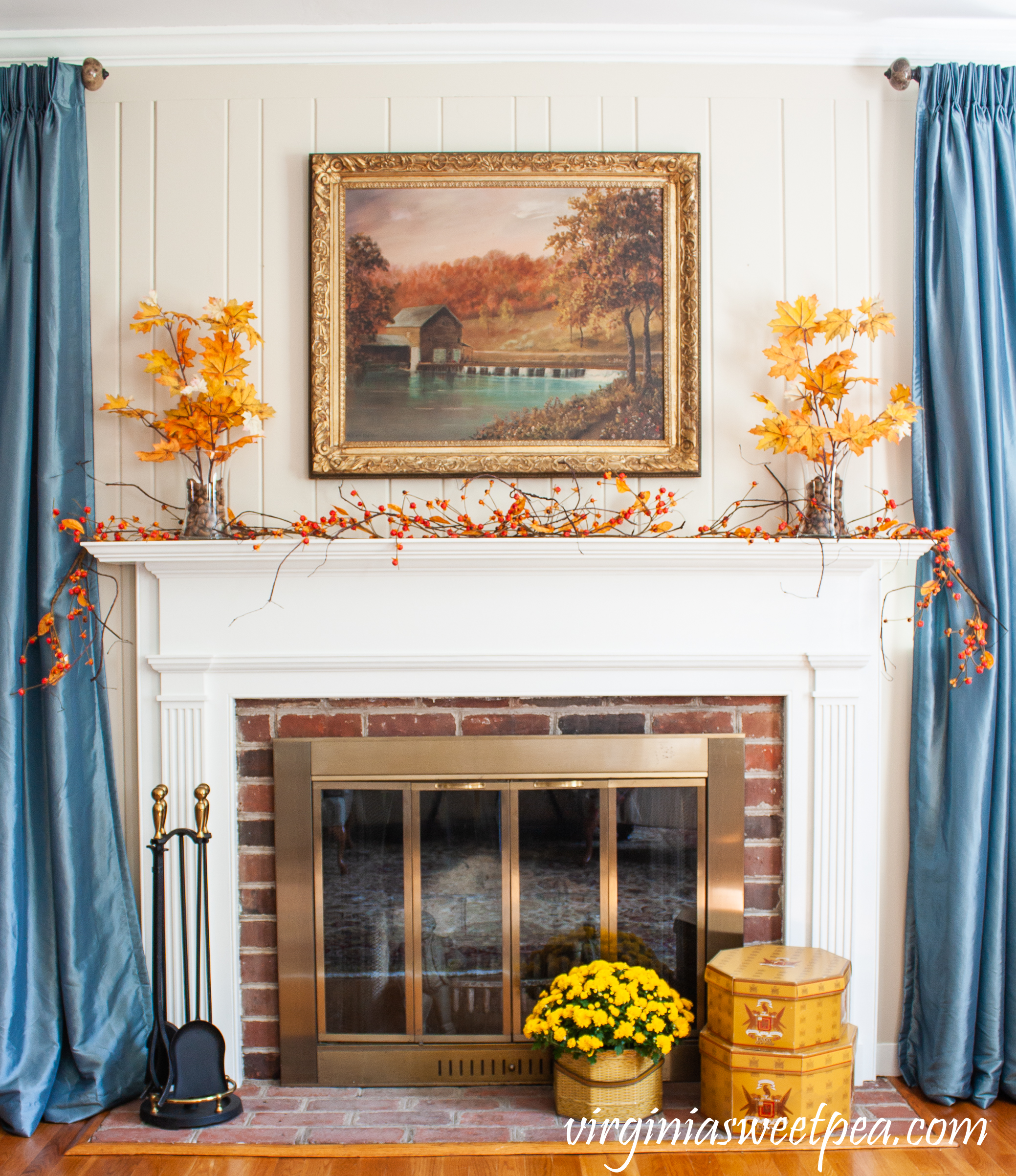 Traditional fall mantel with mill painting, bittersweet, leaves anchored in glass vases with acorns