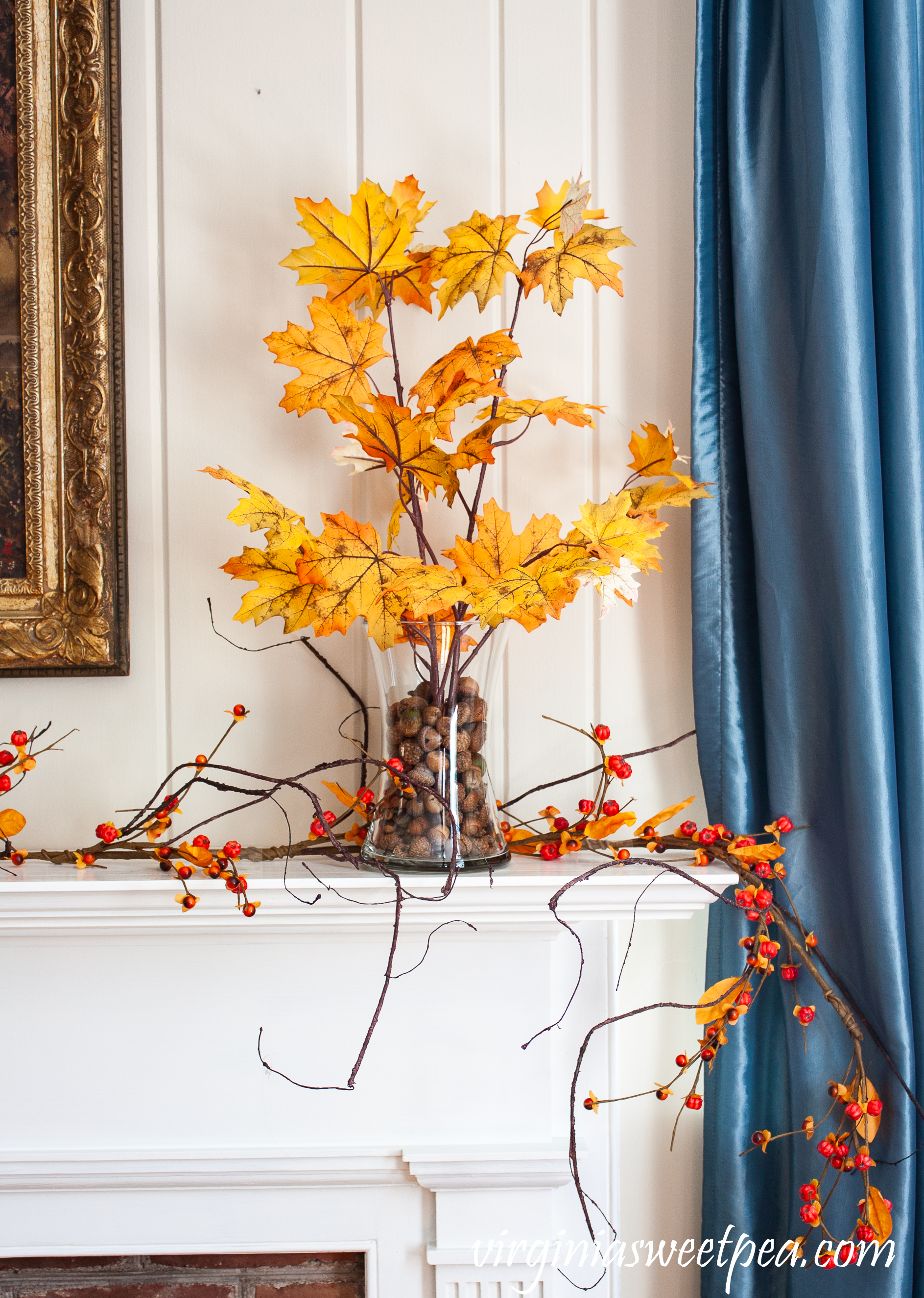 Fall foliage in glass vases anchored with acorns on a mantel with a bittersweet garland