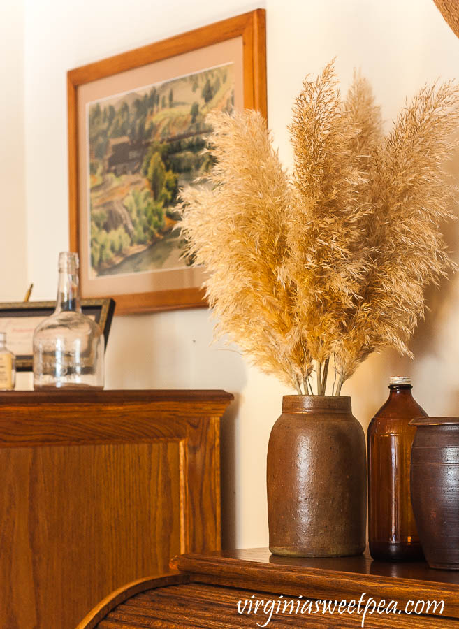 Pampas grass in an antique crock with an amber vintage Clorox bottle and a Emlyn Edwards painting.