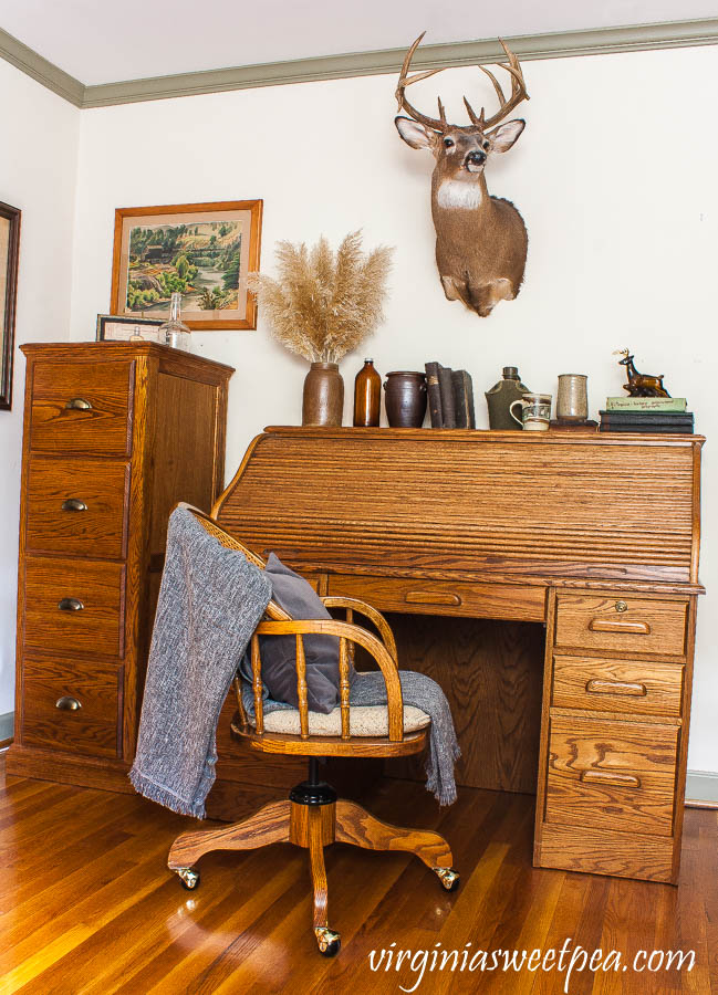 A roll top oak desk is decorated with vintage with a masculine and cabin theme.