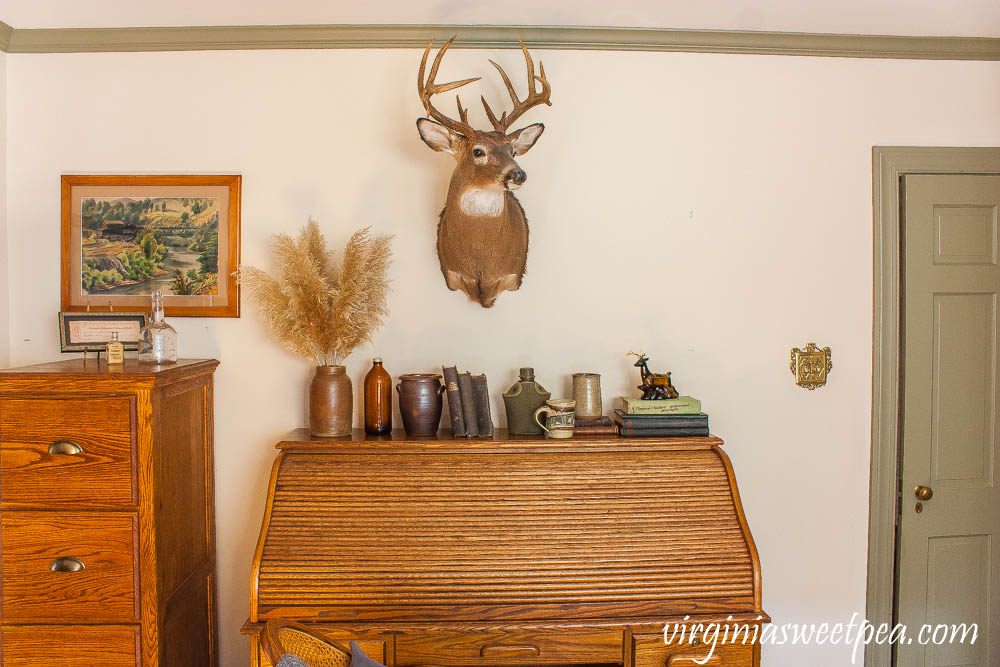 Desk decorated with a cabin theme including a deer head, old books, and pottery.