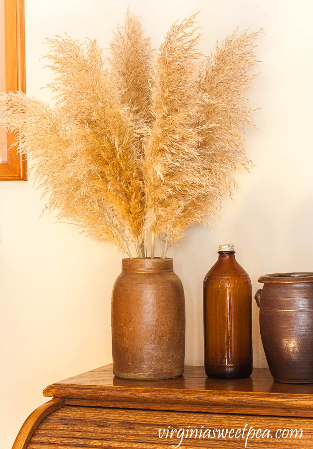 Pampas grass in an antique crock with an amber Fleecy White Clorox bottle and a pottery jar from North Carolina