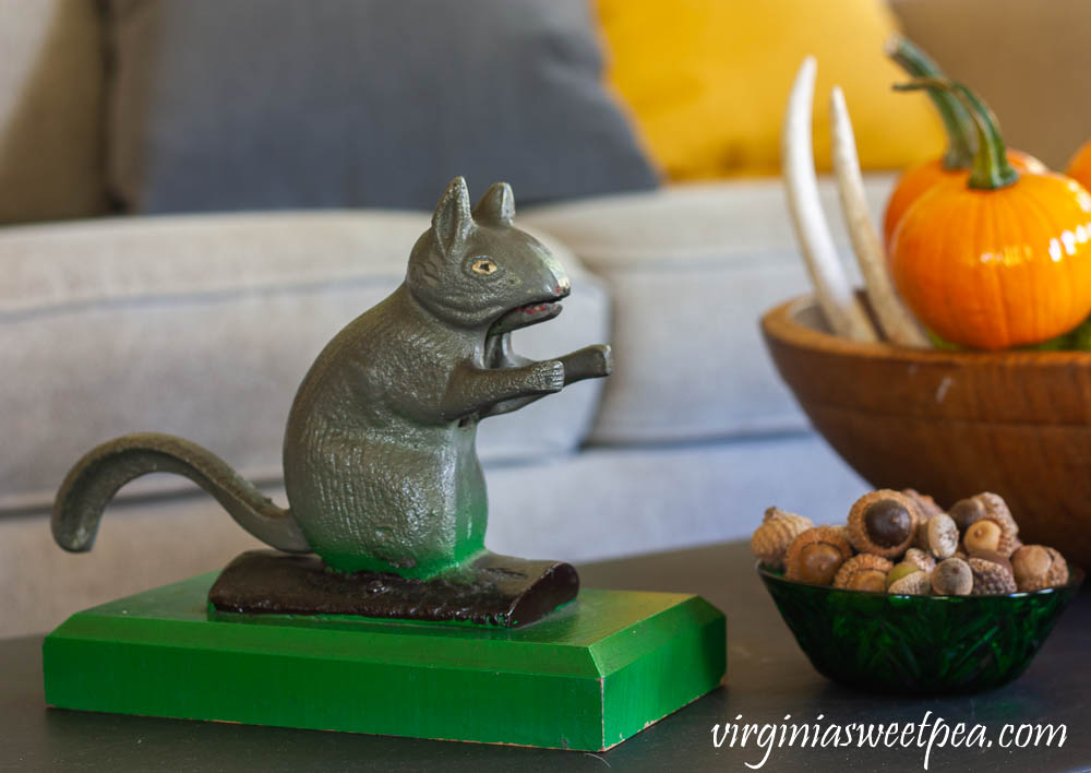 Vintage squirrel nutcracker on a coffee table decorated for fall with vintage.