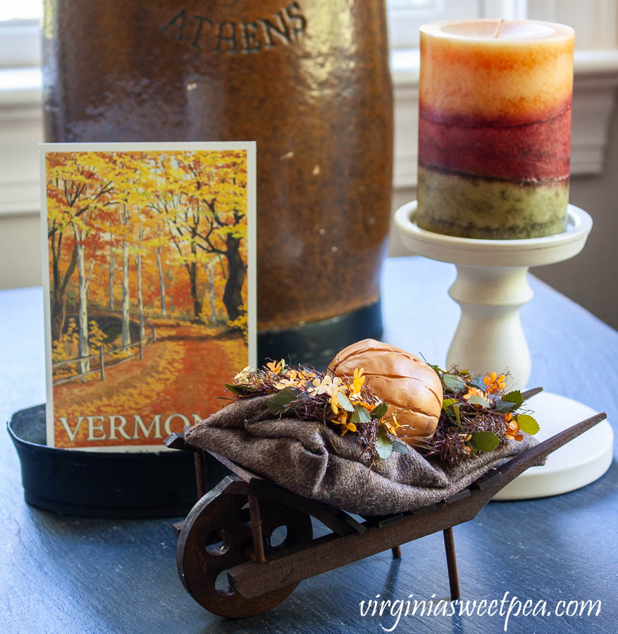 Vermont themed fall vignette - Vermont postcard with a Byer's wheelbarrow and a fall candle.