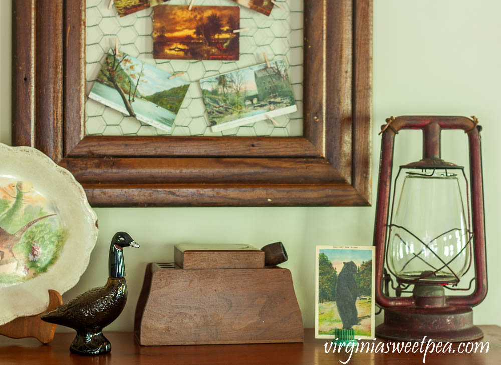 Fall Vignette with an Avon Goose Bottle, vintage pipe and tobacco box, antique lantern, and a vintage bear postcard.