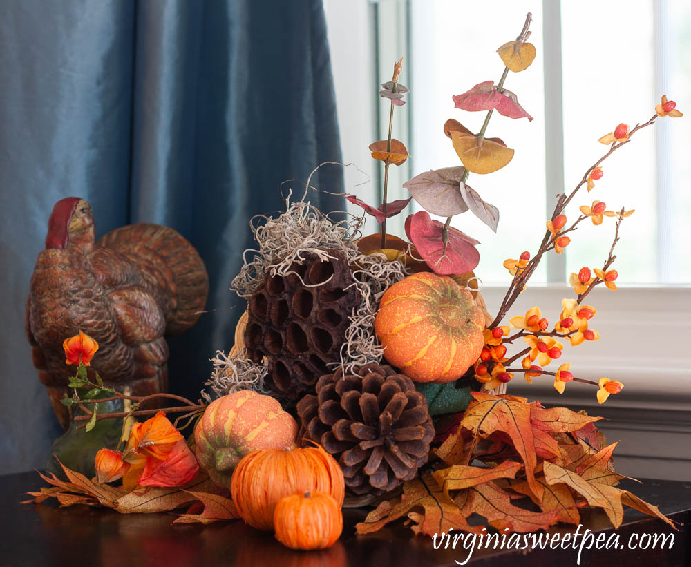 Thanksgiving decor using a turkey figure and a cornucopia filled with bittersweet, japanese lantern, eucalyptus, pumpkins, lotus pods, and pine cones.