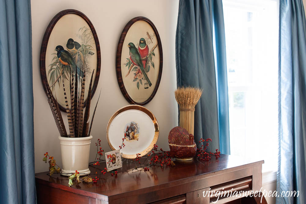 Thanksgiving Decor with Vintage - An antique chest is decorated with a vintage turkey platter, crock filled with pheasant feathers, a vintage Thanksgiving postcard, a wheat sheaf, and a vintage turkey lidded dish.