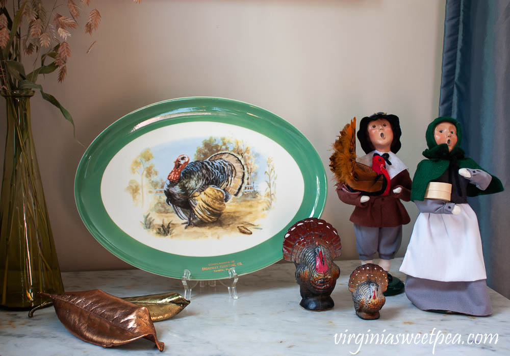 Thanksgiving decor using a vintage turkey platter, Byers' Choice pilgrims, and vintage turkey candles.