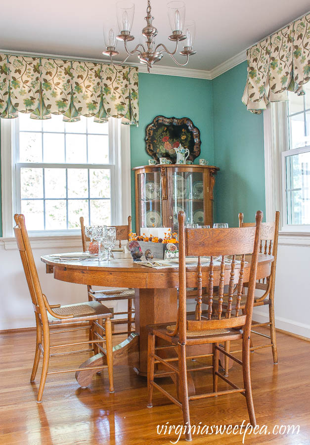 Antique oak dining room table and chairs with a table set for Thanksgiving.