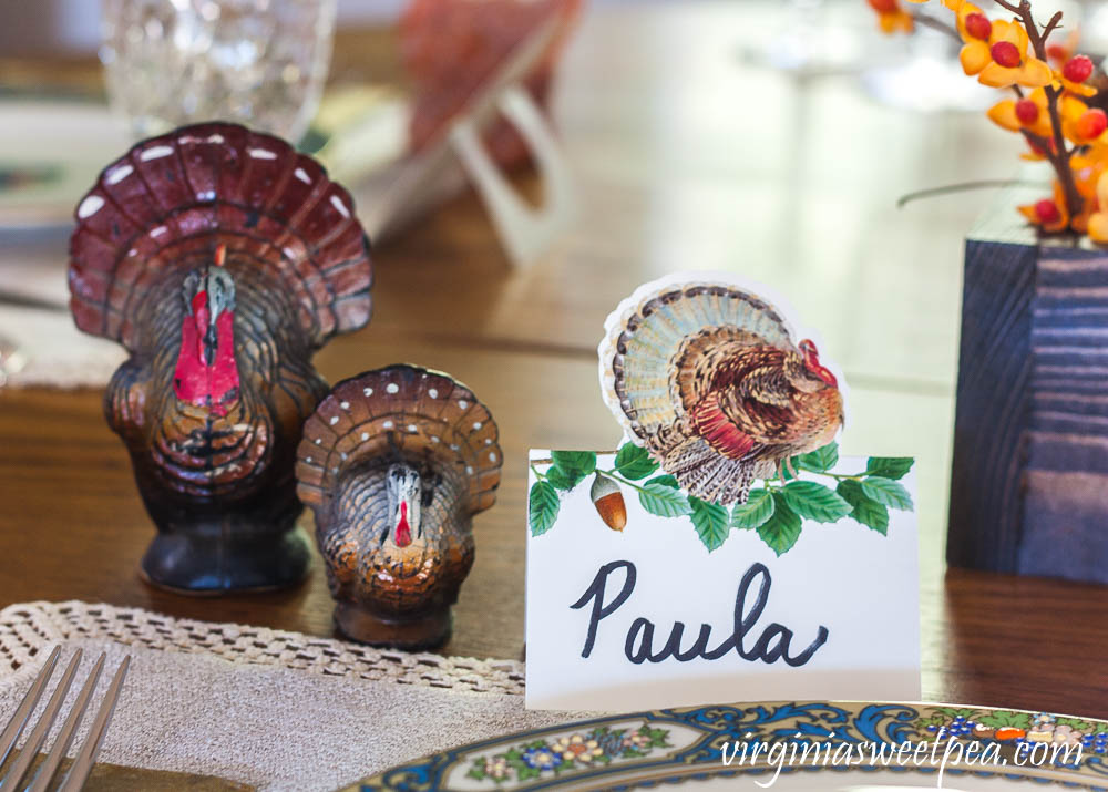 Thanksgiving place setting with a Caspari turkey place card and vintage turkey candles.