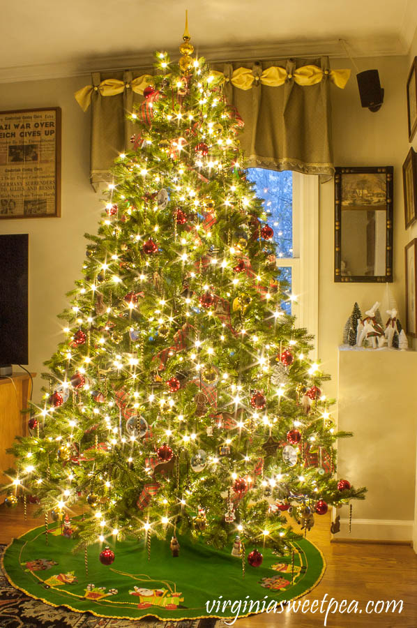 Family room Christmas tree at night decorated with ornament collected over 25 years.