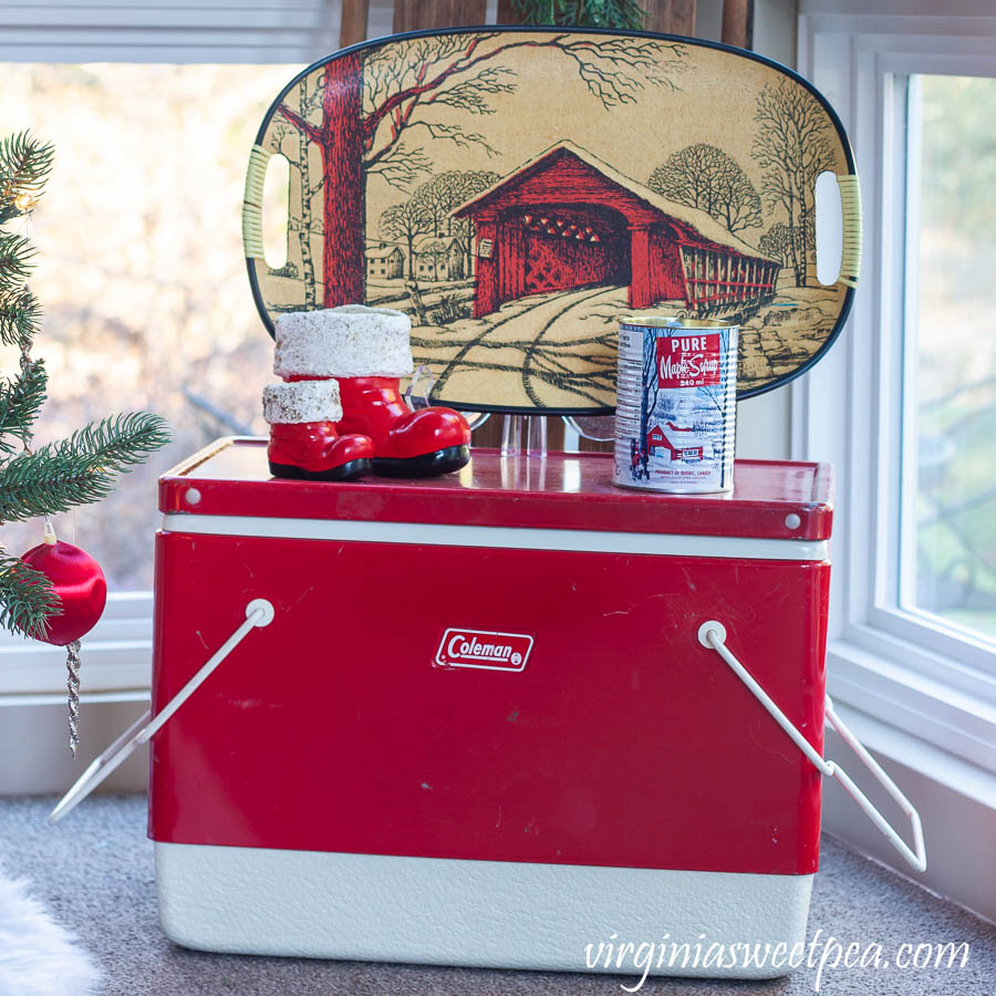 A Very Vintage Christmas on the Porch - Vintage Coleman cooler with vintage Santa boots, a vintage covered bridge tray, and a maple syrup scented candle in a maple syrup can