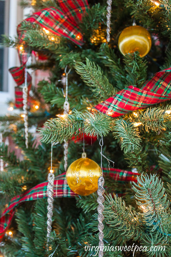 Christmas tree decorated with 1970's satin yellow and red balls, plaid ribbon, and glittered icicles.